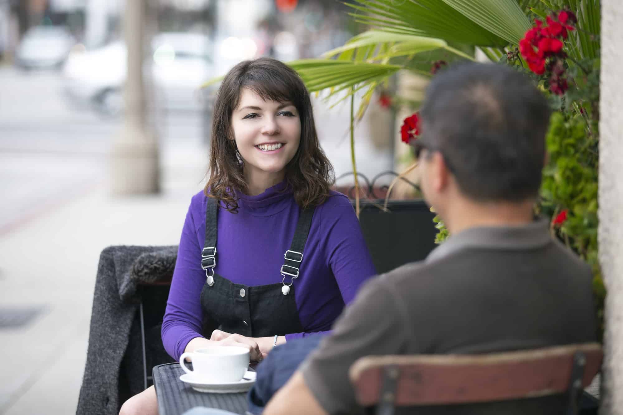 woman talking to a man at a cafe table