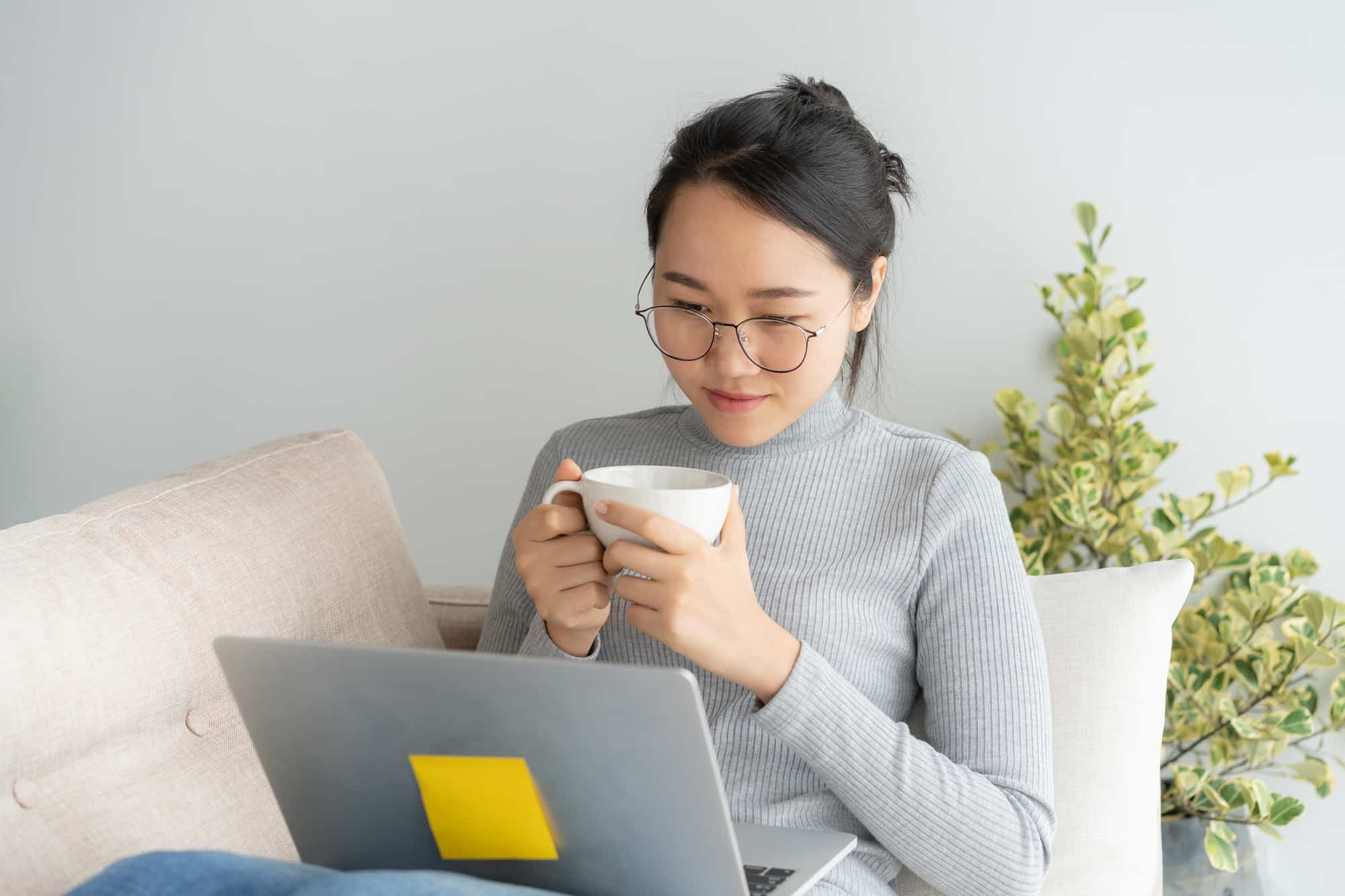 woman with glasses holding a cup reading on her laptop