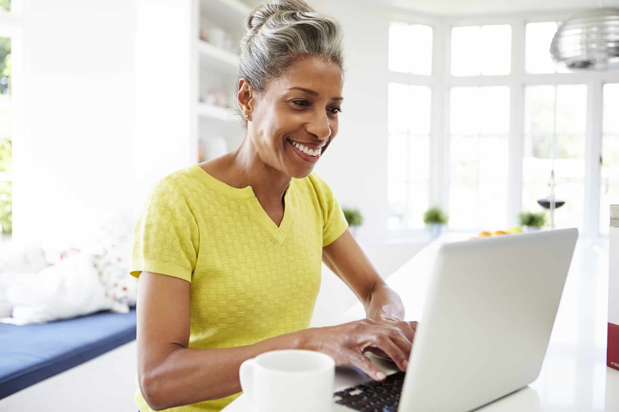 an older woman smiling while working on her laptop