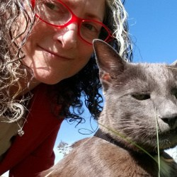 Woman with glasses and curly hair smiles at the camera next to her gray cat